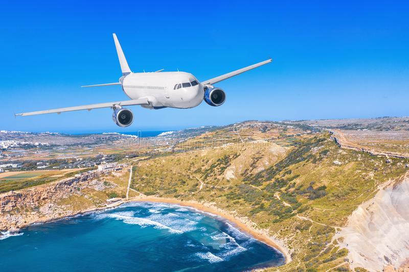Passenger airplane flying over beautiful blue sea water, along the coast of the island beach, summer holiday vacation traveling.  stock image