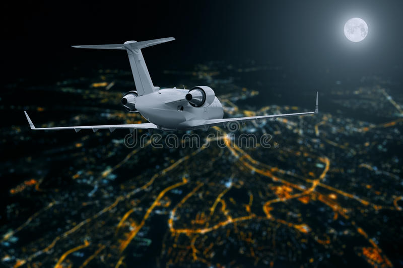 Passenger airplane flying over city at moon night royalty free stock image