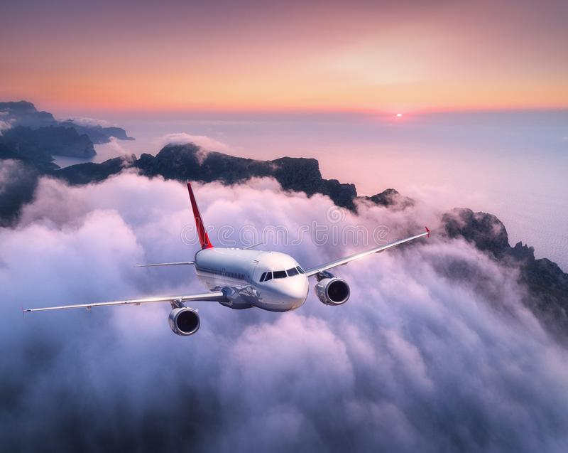 Passenger airplane is flying over clouds at sunset. Landscape with white airplane, low clouds, sea coast, purple sky at dusk. Aircraft is landing. Business stock images