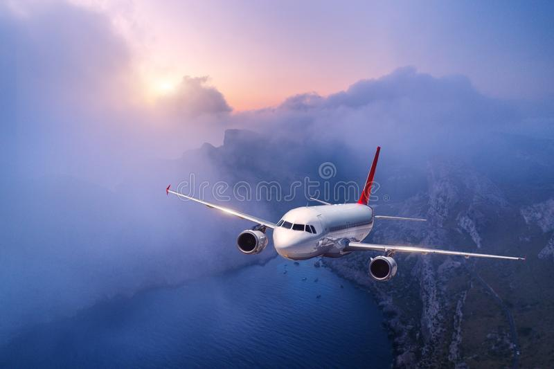 Passenger airplane is flying over clouds at sunset. Landscape with white airplane, low clouds, sea coast, purple sky at dusk. Aircraft is landing. Business royalty free stock photos