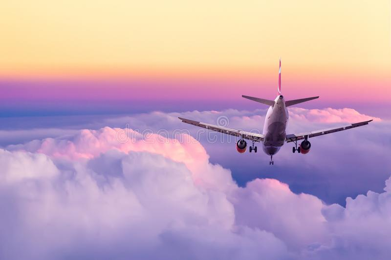 Passenger airplane landing against amazing yellow and pink colorful sky with clouds during sunset. Travel background.  stock photography