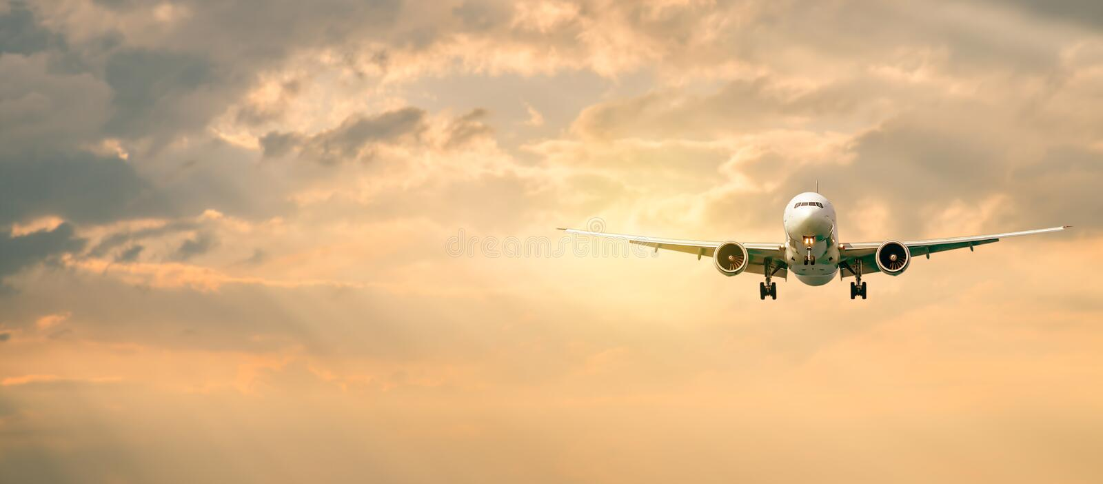 Passenger airplane. Landscape with Front of white airplane is flying in the orange sky with clouds, Passenger aircraft is landing royalty free stock photo