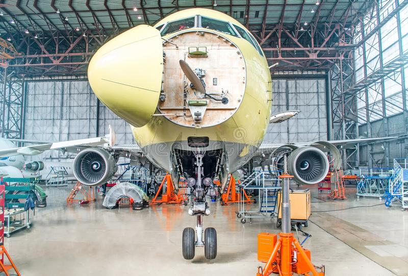 Passenger airplane on maintenance of engine and fuselage check repair in airport hangar. With an open hood on the nose under the c. Ockpit of pilots royalty free stock photography