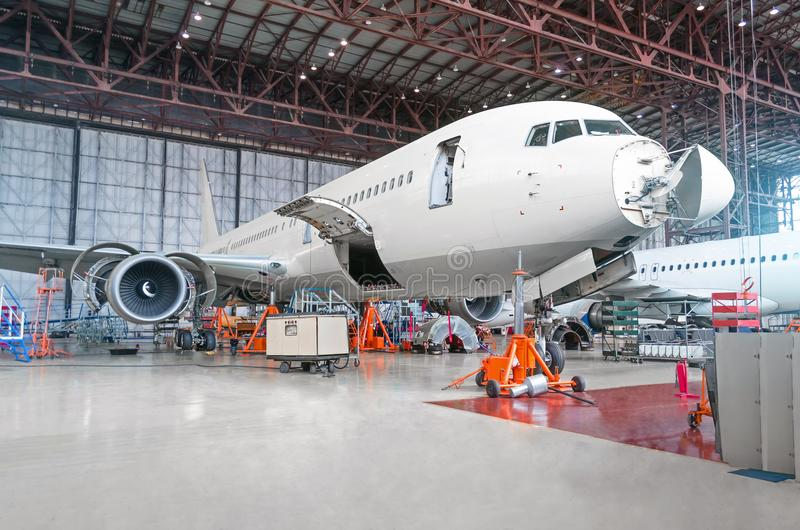 Passenger airplane on maintenance of engine and fuselage repair. In airport hangar. Aircraft with open hood on the nose and engines, as well as the luggage royalty free stock image