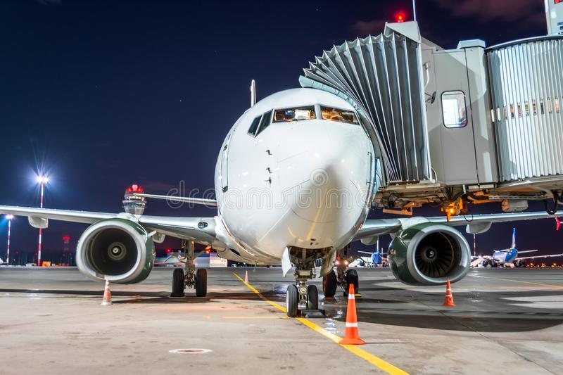 Passenger airplane at the telescope aerobridge at the airport night flight service. royalty free stock photos