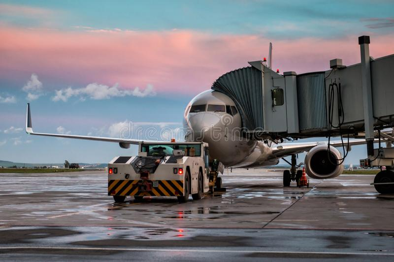 Passenger airplane and tow truck at the jet bridge. Front view stock photos