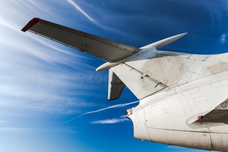 Tail of aircraft. White tail of aircraft on blue sky background. Passenger airplane, view with behind. Tail of an aircraft royalty free stock photo