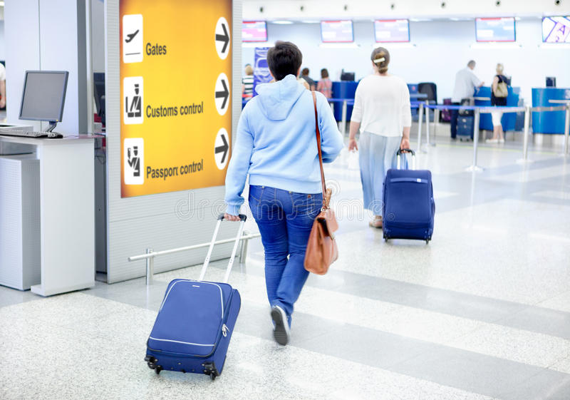 Passenger at the Airport goes with Luggage. Passengers at the Airport go with Suitcase and Leather Bag royalty free stock photos
