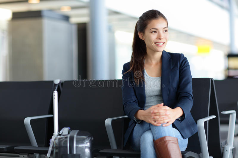 Passenger Asian woman in airport - air travel. Passenger. Asian woman in airport waiting for air travel. Young business woman smiling sitting with travel royalty free stock photography