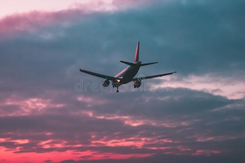 Passenger or cargo plane flies against the background of a red s stock photography