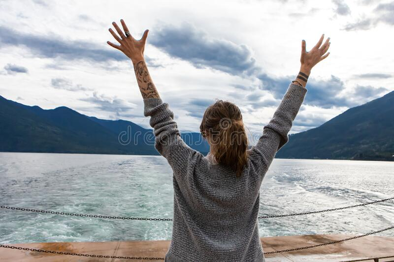 Passenger on the deck of a Canadian ferry. Close up from behind of a young long haired lady on the deck of a passenger ferryboat. Arms with tattoos raised and stock photo