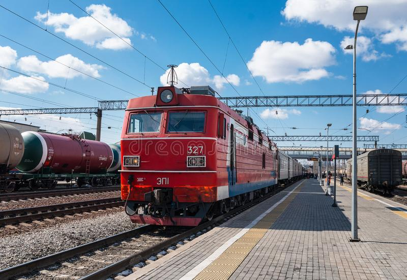 Passenger electric train arrives at the city railway station on a sunny day. Diagonal perspective view. stock image