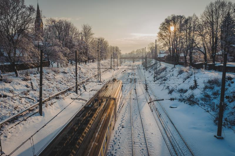 Passenger electric train on the railway at winter sunset behind trees. stock photo