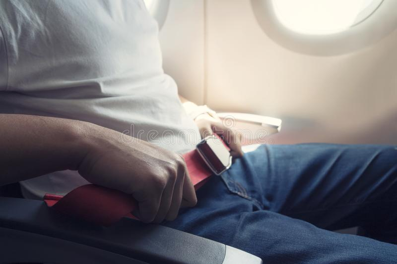 Passenger fastening seat belt while sitting on the airplane for safe flight. Safety travel.  royalty free stock photos