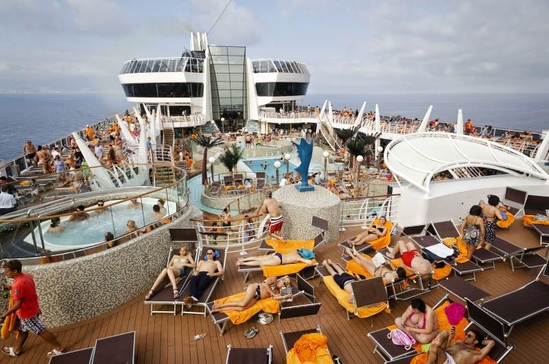 PASSENGER FERRY, MIDSEA, SPAIN - JUNE 09, 2012: Passengers enjoy at swimming pool on upper deck of The luxury cruise MSC SPLENDIDA royalty free stock image