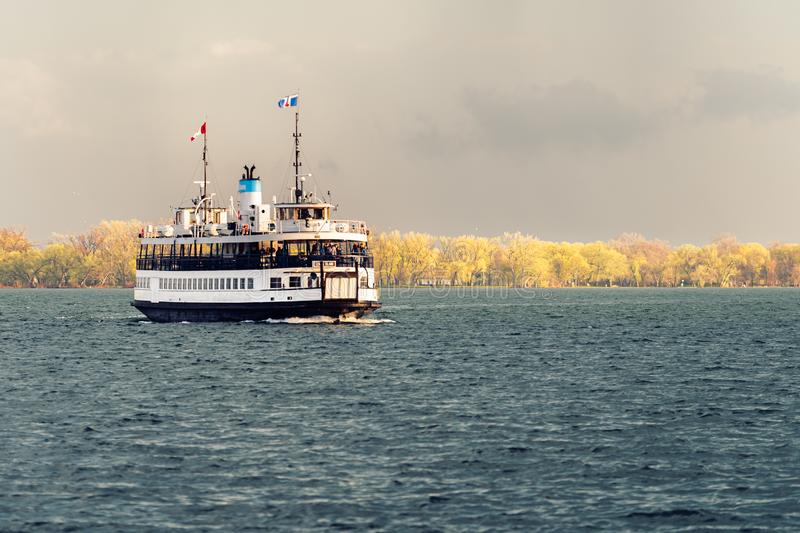 A passenger ferry sails across Toronto harbour after a storm. A passenger ferry sails across Toronto harbour towards its berth after a storm stock image