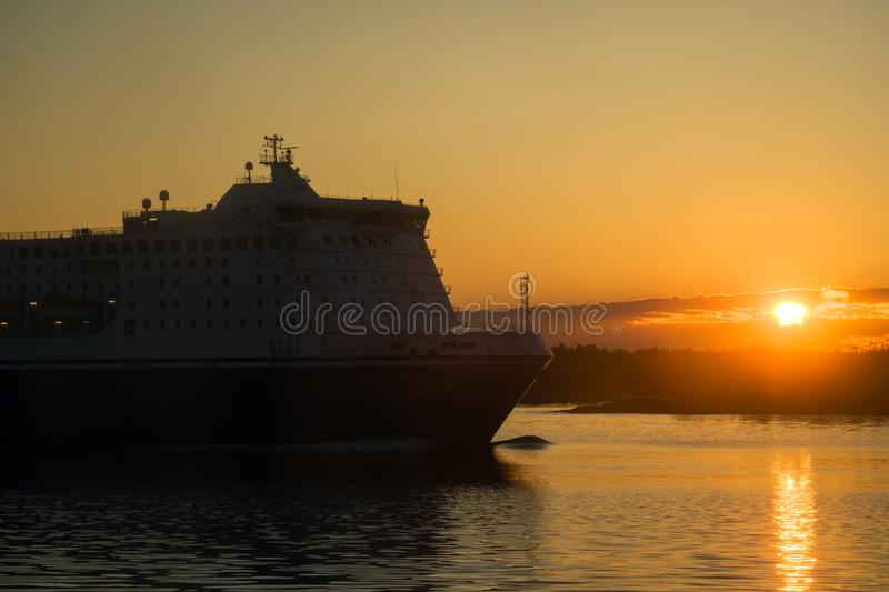 Passenger and freight ferry. Against a sunset in the Baltic sea stock photos