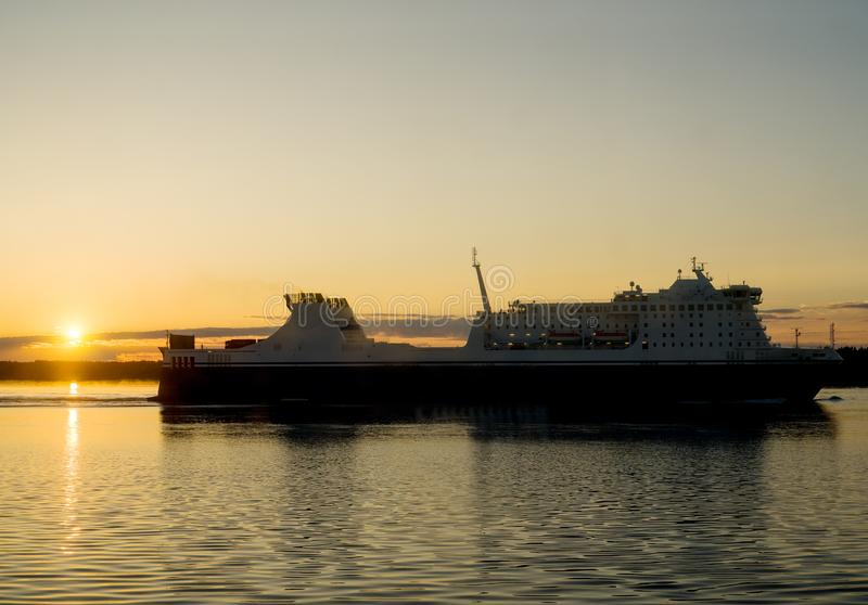 Passenger and freight ferry. Against a sunset in the Baltic sea stock image