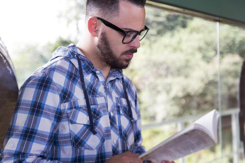 Passenger guy wearing glasses reading a book. Concept of concentration, journey, motivation. Bearded passenger guy wearing glasses reading a book in train stock photography