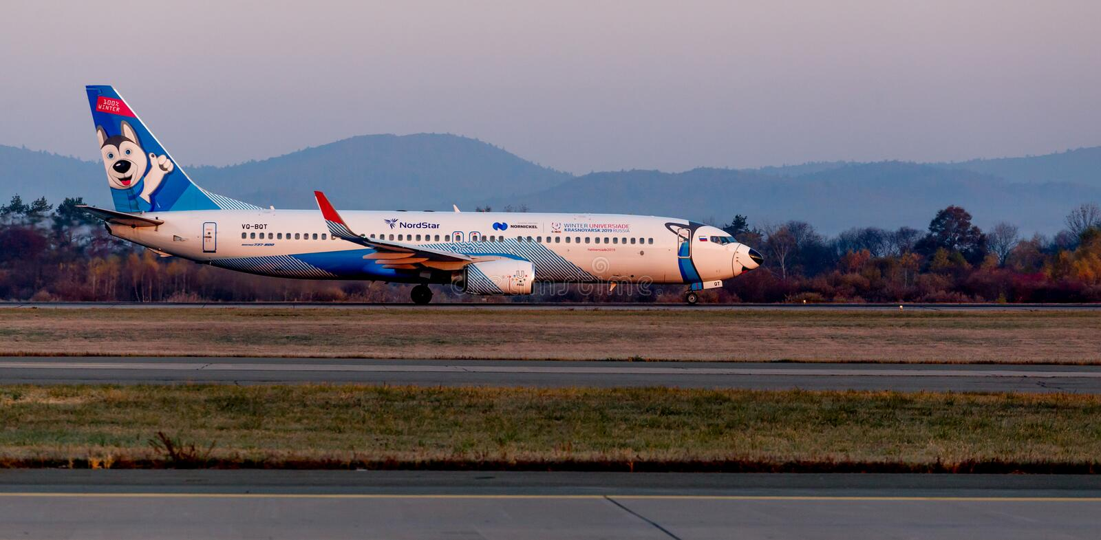 Passenger jet aircraft Boeing 737-800 of NordStar Airlines on the runway. Fuselage is painted as dog Siberian Husky. Russia, Vladivostok, 10/13/2017. Passenger stock photography