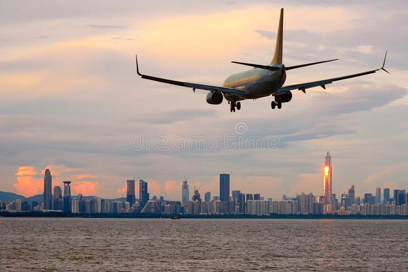 Passenger jet airliner plane arriving or departing Shenzhen, China. Shenzhen skyline with a commercial passenger jet airliner plane arriving or departing, sunset royalty free stock photo