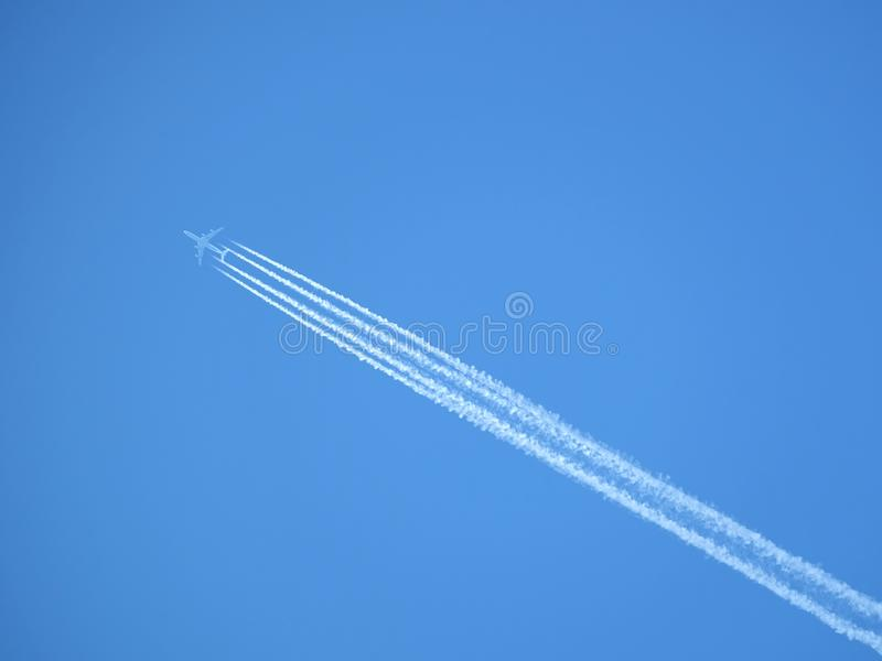 Passenger jet flying in clear blue sky, leaving white trail royalty free stock photos