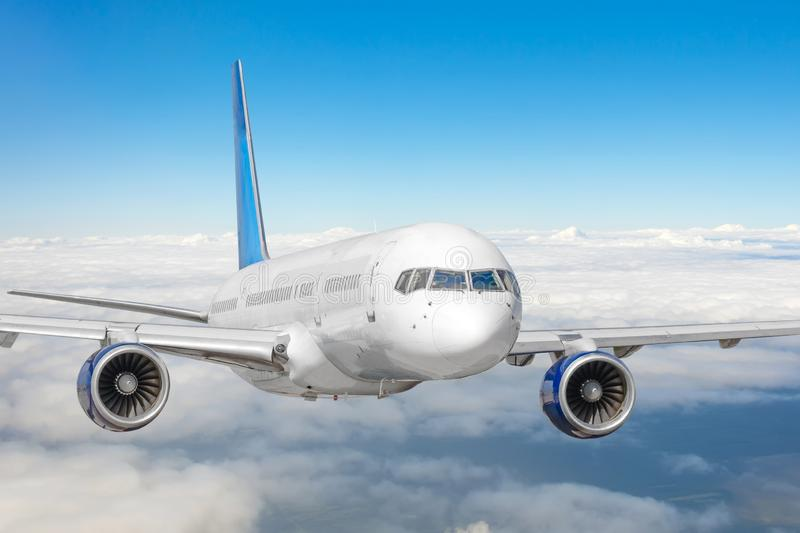 Passenger jet plane in the blue sky. Aircraft flying high through the cumulus clouds. Close up view airplane in flight royalty free stock photo