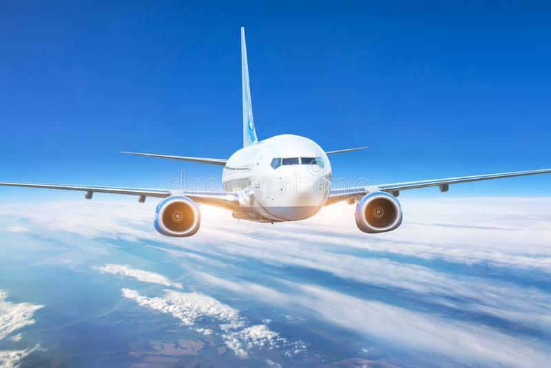 Passenger jet plane in the blue sky. Aircraft flying high through the cumulus clouds. Close up view airplane in flight stock photo