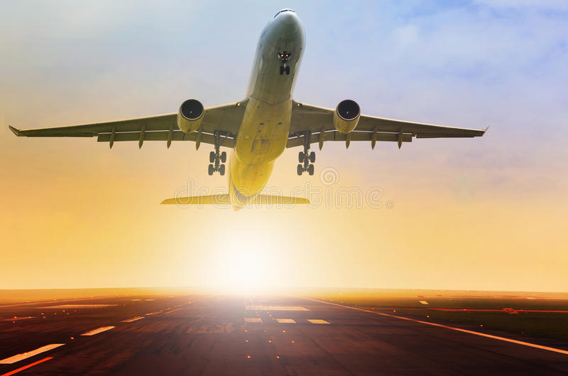 Passenger jet plane take off fron airport runway with beautiful. Light of sun rising behind royalty free stock image