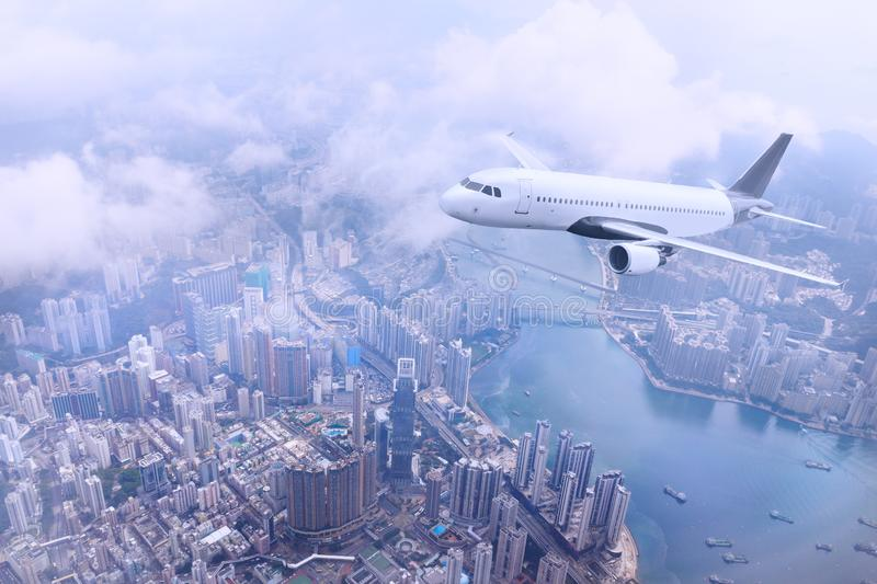 Passenger plane fly to Hong Kong Island. Aerial view at cityscape. Airplane over urban skyline. Concept of travel and air transportation royalty free stock photo