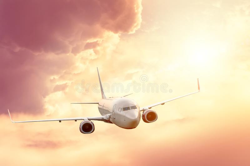 Passenger plane in the sky at sunrise or sunset, vacation and travel.  stock images