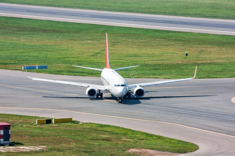 Passenger plane turns on taxiway stock photos