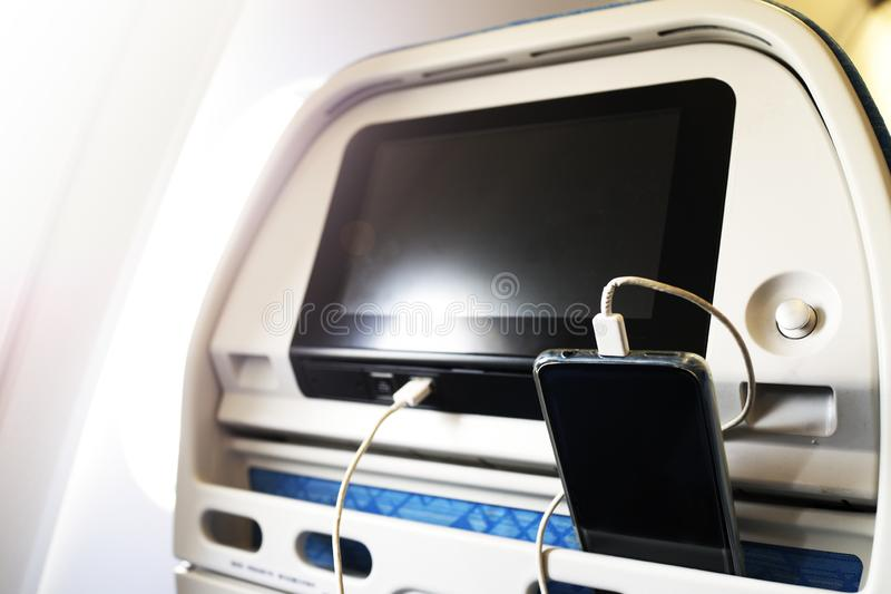 Passenger on a plane using the charger for charge smart phone during flight. Charging station on plane. Horizontal royalty free stock image
