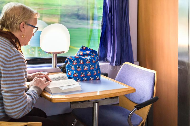 A passenger reading a book sitting at the dining car of a Greek stock images