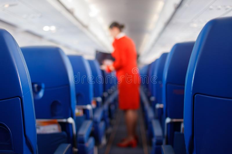 Passenger seat in airplane, Interior of airplane and stewardess background. Stewardess renders services for passengers. royalty free stock images