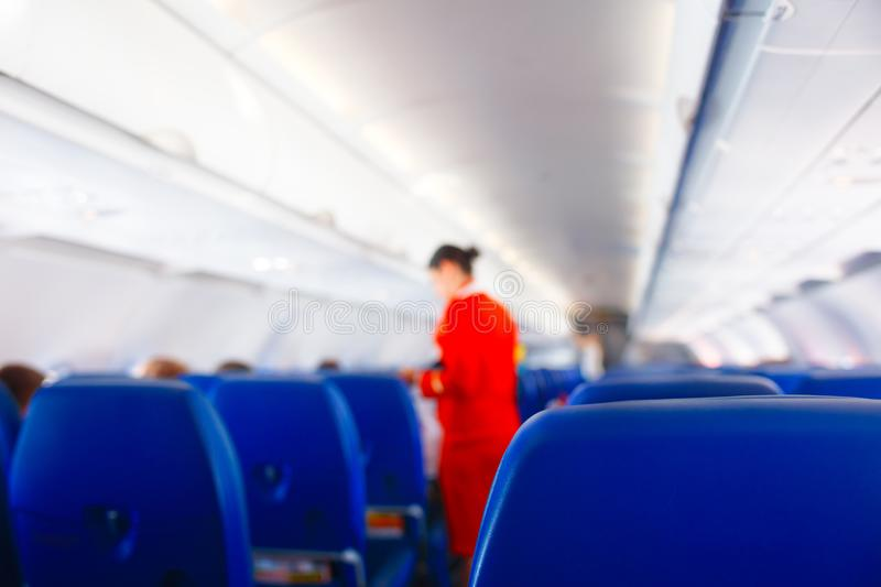 Passenger seat in airplane, Interior of airplane and stewardess background. Stewardess renders services for passengers. Service stock photo