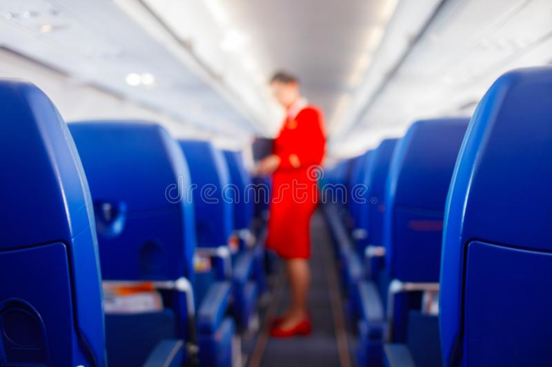 Passenger seat in airplane, Interior of airplane and stewardess background. Stewardess renders services for passengers. royalty free stock photos