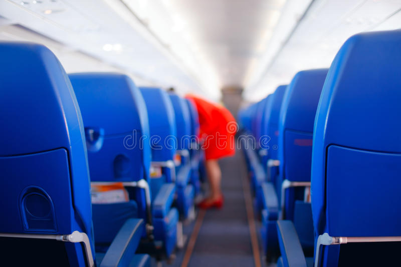 Passenger seat, Interior of airplane with passengers sitting on seats and stewardess walking the aisle in background. stewardess s royalty free stock photography
