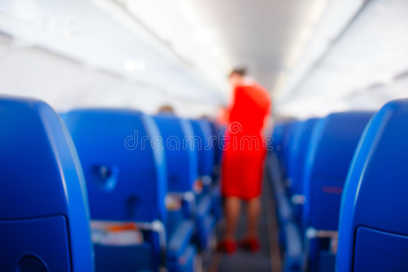 Passenger seat, Interior of airplane with passengers sitting on seats and stewardess walking the aisle in background. stewardess s stock images