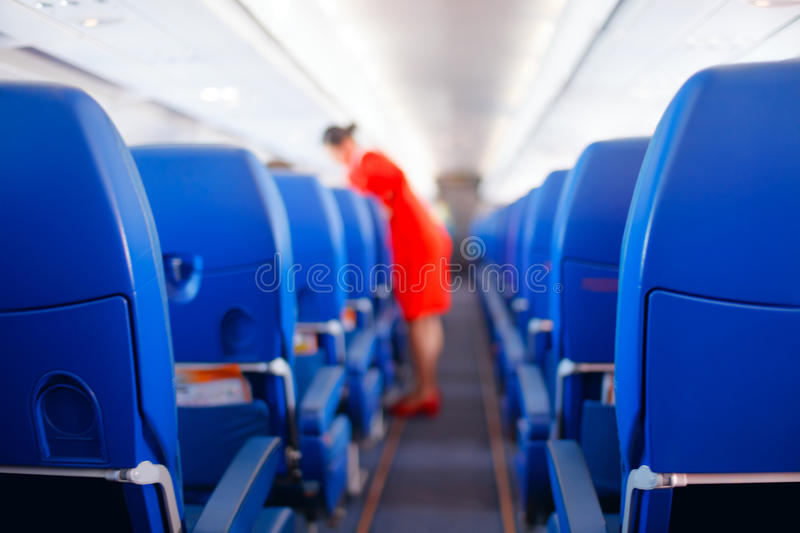 Passenger seat, Interior of airplane with passengers sitting on seats and stewardess walking the aisle in background. stewardess s stock photo
