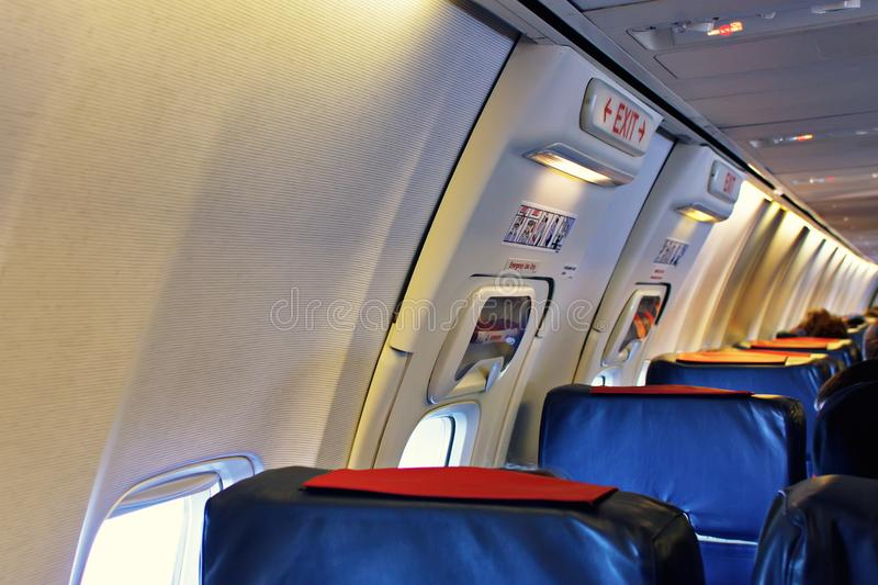 Passenger seat, Interior of airplane with passengers sitting on seats. stock image