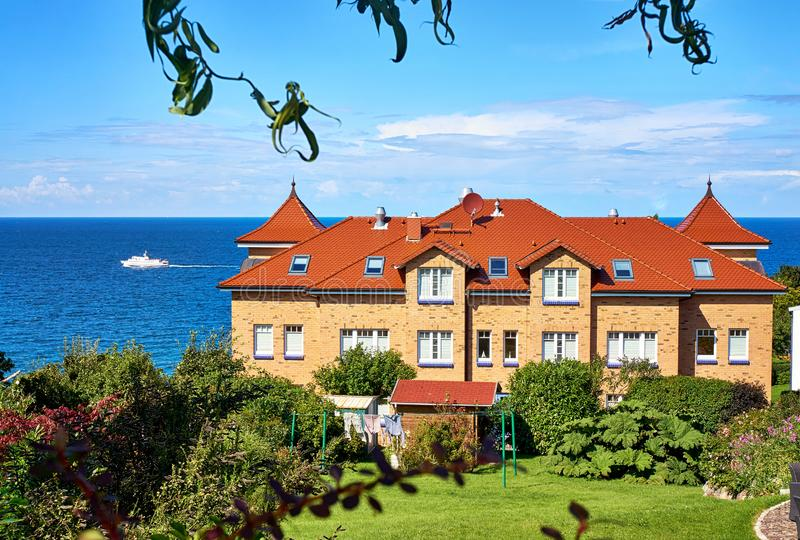 Passenger ship on the Baltic Sea behind the residential building. Living in Lohme on the Baltic Sea on the island of Rügen stock photography