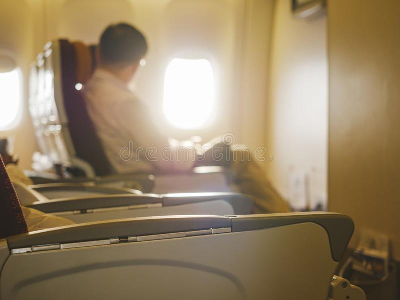 Passenger sit on airplane look through window Businessman travel stock photo