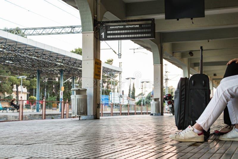 A passenger sitting waiting for a train at Larissa Train Station stock photo