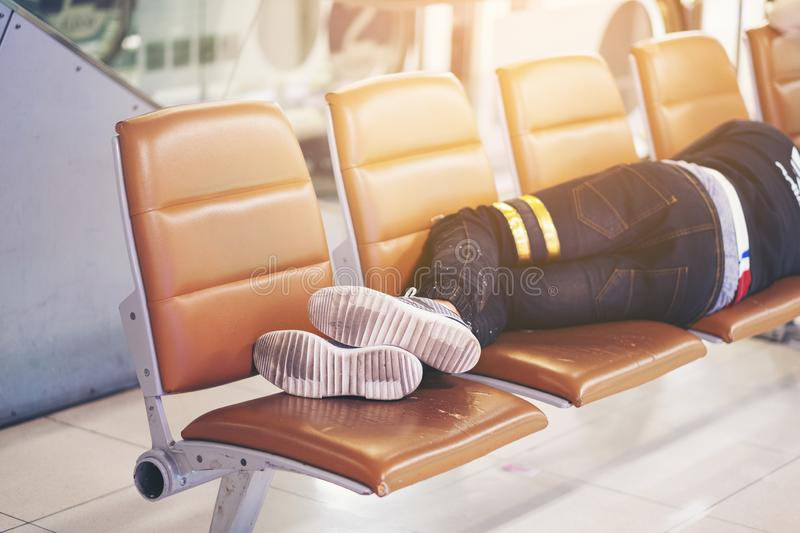 Passenger sleep on a bench in airport terminal waiting for his flight, be tried. Ok stock image