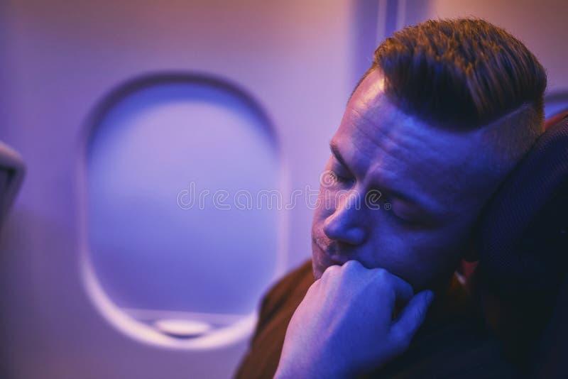Passenger sleeping during night flight stock photo