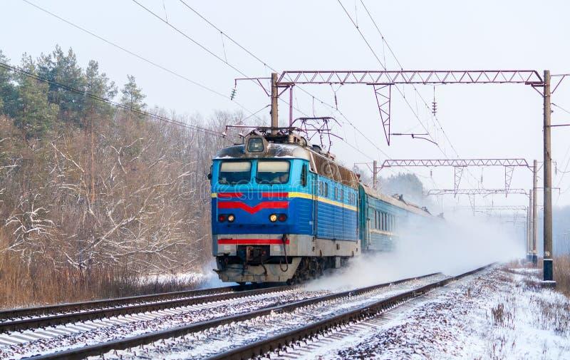 Passenger train moving along the snow track. Passenger train rapidly moving along the snow track. Ukraine royalty free stock image
