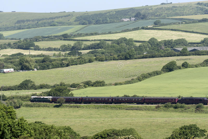 Passenger train passing through countryside. Diesel engine pulling passenger coaches through the Dorset countryside at Harmans Cross on the Swanage Railway line royalty free stock images
