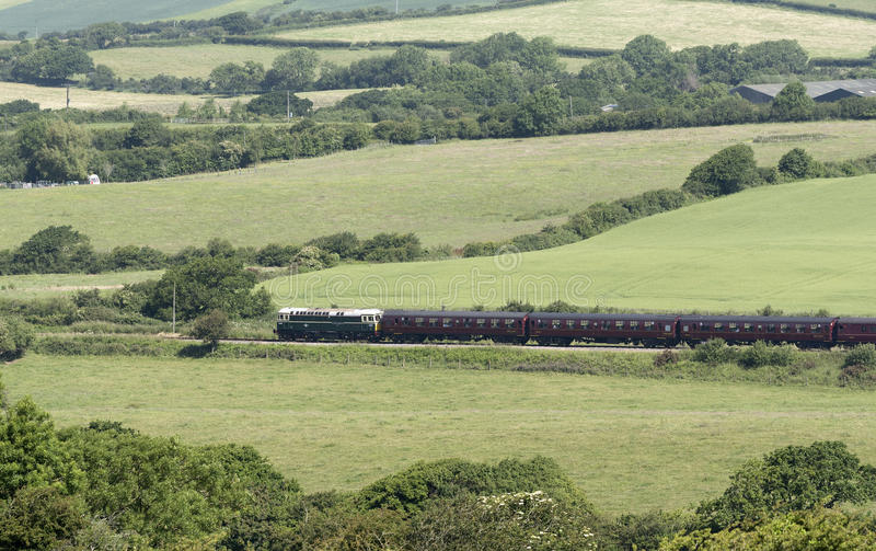 Passenger train passing through countryside. Diesel engine pulling passenger coaches through the Dorset countryside at Harmans Cross on the Swanage Railway line royalty free stock photography