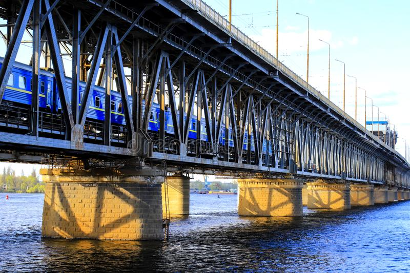 The passenger train  rides along a two-level bridge and a railway across the Dnieper  River in the Dnipro city in spring. The passenger train  rides along a two royalty free stock image